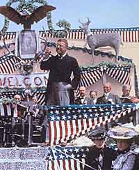 Teddy Roosevelt speaking on bunting-draped stage
