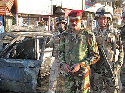 Moments after Iraqi soliders warned them away from their armored sedan, NPR correspondent Ivan Watson and his team watched as the car exploded. Iraqi Lt. Mohamed Jabbour, pictured with the burned-out car, gave the warning. (Photo © 2008 NPR News/Ivan Watson.)