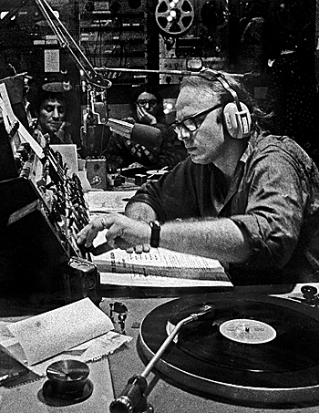 "Fass, behind the mic, ""used the mixing console the way an artist uses paint,"" says Steve Post. Pictured in background is Abbie Hoffman, a frequent guest on Radio Unnameable. (Photo: Robert Altman)"