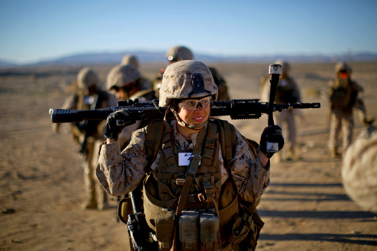 Sgt. Courtney White carries her machine gun before a live-fire exercise. (Photo: David Gilkey/NPR)
