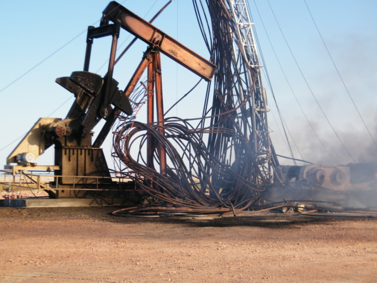 From the June episode of Reveal, a North Dakota rig still smoldering the day after a 2011 explosion. Photo: Occupational Safety and Health Administration.