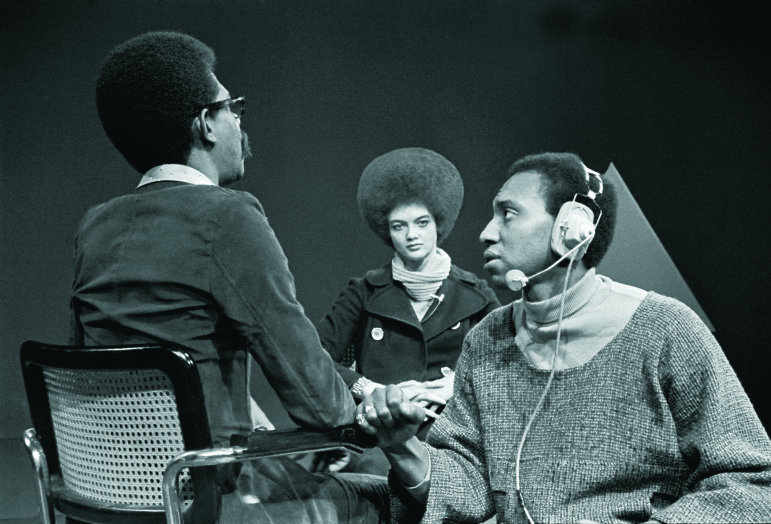 Soul! host Ellis Haizlip takes a break from interviewing Kathleen Cleaver of the Black Panthers while a sound engineer checks the mic. (Photo © Chester Higgins Jr. All Rights Reserved)