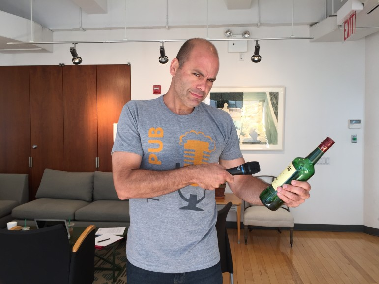 Mike Pesca wears a Pub t-shirt while interviewing a bottle of whiskey, as one does. (Photo: Andrea Silenzi, Slate)