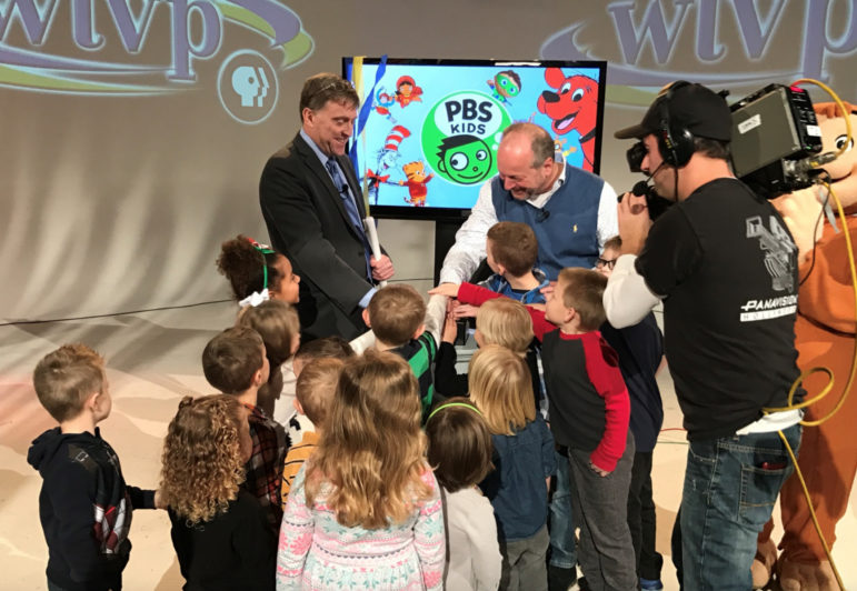 WTVP President Moss Bresnahan, left, and ??, board chair, help kids flip a prop switch to symbolically launch the channel. (Photo: WTVP)