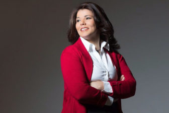 Celeste Headlee stands with her arms crossed and looks to her right,