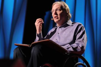 John Hockenberry gestures with his right hand as he speaks from a stage with a blue backdrop.