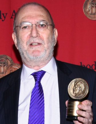 Leonard Lopate holds a Peabody medal.