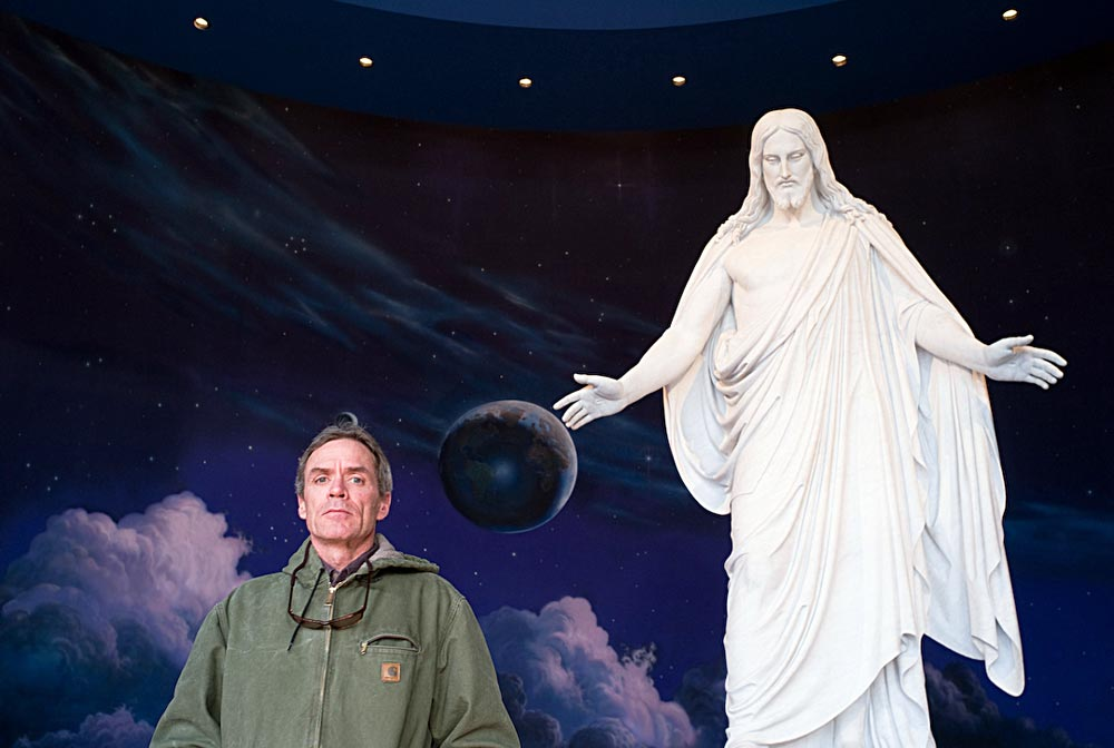 Scott Carrier poses with Jesus Christ scuplture at Temple Square's Visitor Center, Salt Lake City. Photo: Julian Cardona