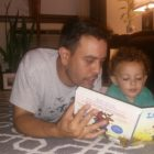 A 413 Families participant reads to his child.